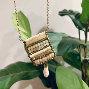 Beaded gold pendant necklace.
